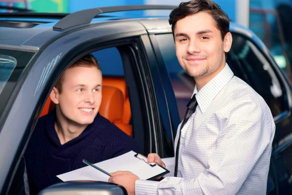 Car salesmen with young car buyer
