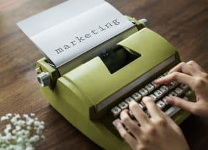 Person Typing On Typewriter with the word marketing already typed