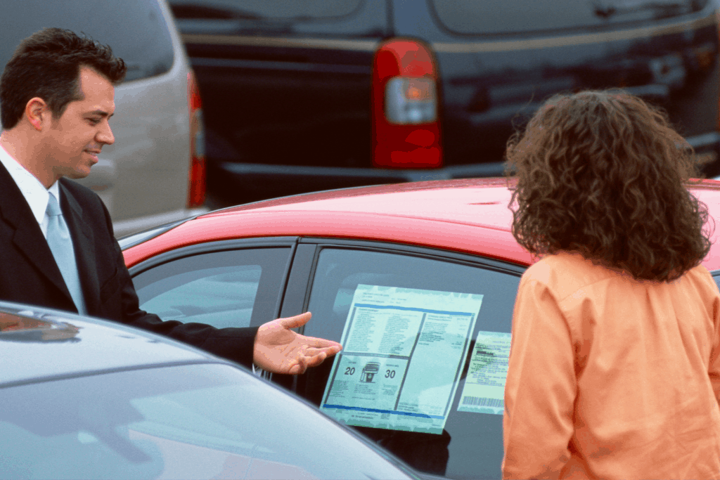 Car salesmen showing woman the window sticker of a new red car.